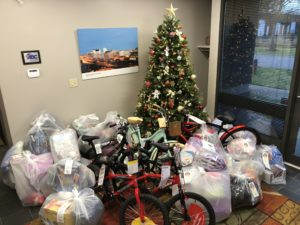 Dozens of donated gifts, including bikes, surround a decorated Christmas tree.
