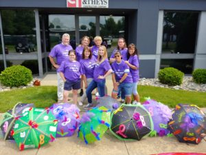 Clancy & Theys employees stand outside their office in matching purple team shirts