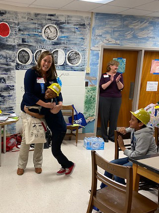 Cassie hugs the second place winner while the teacher and other students applaud.